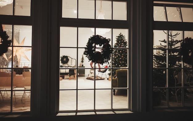 크리스마스 트리 및 창 배경 장식입니다. 창문에 눈과 밝게 장식된 크리스마스 트리가 있는 야경.