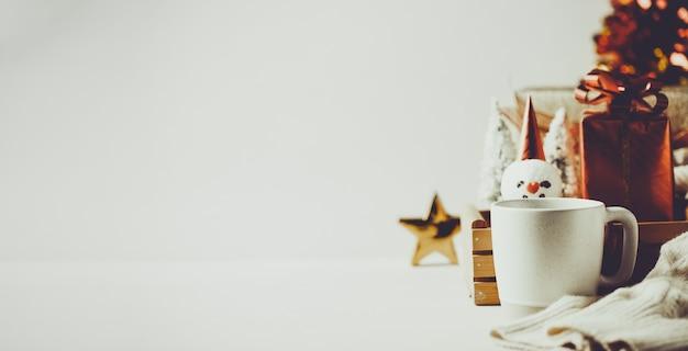 ボケ祭りの明るい背景とマグカップのクリスマスツリーとギフトボックス