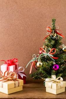 Рождественская елка и подарочная коробка на деревянном столе
