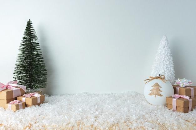 雪の上のクリスマスツリーとギフトボックス