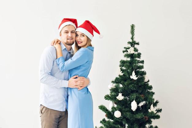 Рождественская елка и концепция праздников - счастливая улыбающаяся семья в шляпах санта празднует дома.