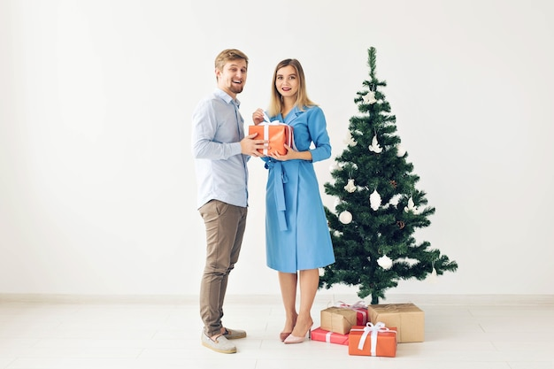 Рождественская елка и концепция праздников - счастливая улыбающаяся семья в шляпах санта-клауса празднует дома.