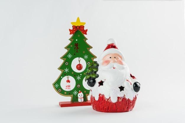 Рождественская елка и санта-клаус с украшениями на белом фоне. рождественский орнамент. выборочный фокус.