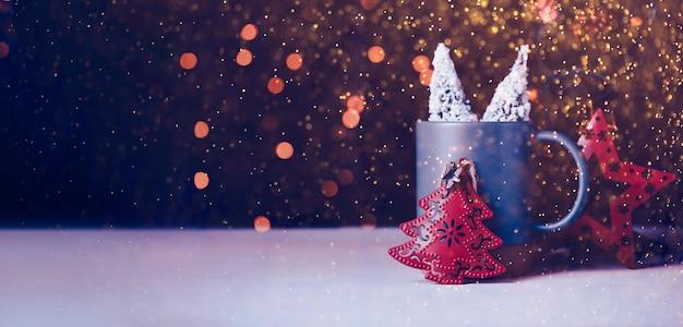 クリスマスツリーとボケ祭りの明るい背景を持つマグカップの星