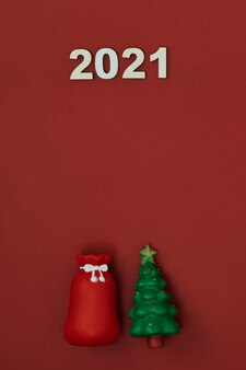 赤い背景の上のクリスマスツリーとおもちゃ