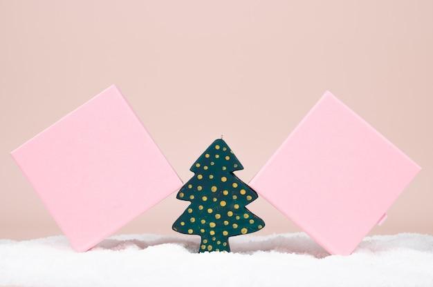 パステルカラーの表面にクリスマスツリーと2つのピンクのギフトボックス。雪の背景に金色のドットと緑の木製のクリスマスツリー。高品質の写真