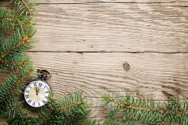 Christmas tree and antique watch on wood