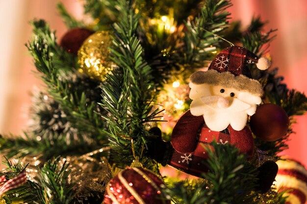 Елка собрана с украшениями. красные, серебряные и золотые шары, подарочные коробки, фонари, дед мороз и другие. выборочный фокус.