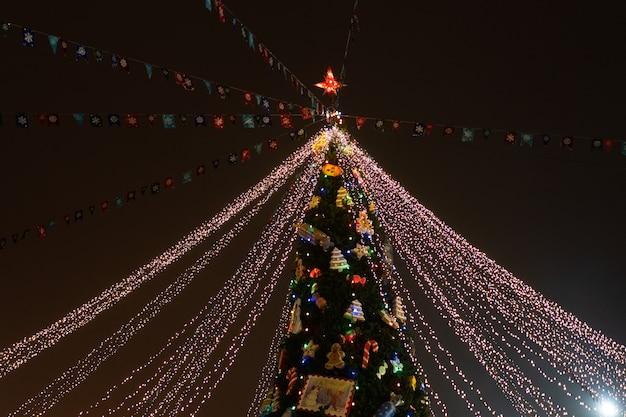 おもちゃとネオンで飾られた夜のクリスマスツリー