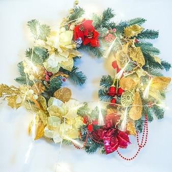 Предпосылка рождественской елки. рождественский венок украшен игрушками на стене.