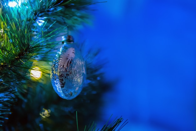 Christmas tree ball decoration hanging on spruce branch surrounded by festive lights. space for text
