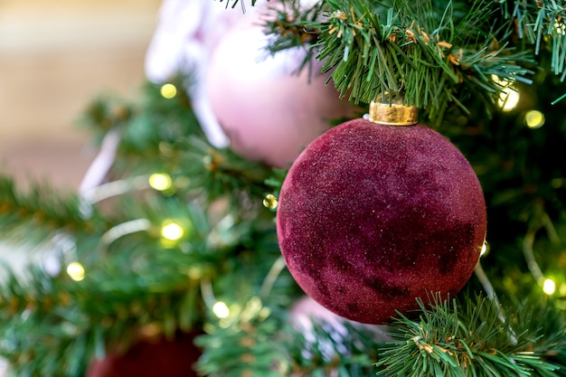 Christmas tree ball hanging on a fir tree with garland new year decoration