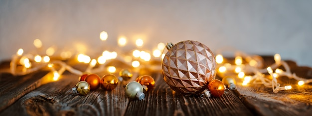 Christmas tree ball toy lay wooden table against a bokeh  holiday lights.