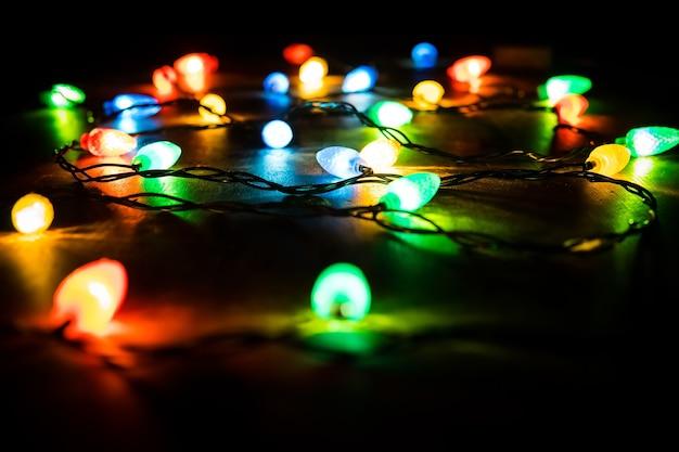 크리스마스 트리 분기와 나무 배경 조명입니다. 복사 공간이 있는 보기. 밤의 어둠 속에서 크리스마스 화환에 색색의 조명