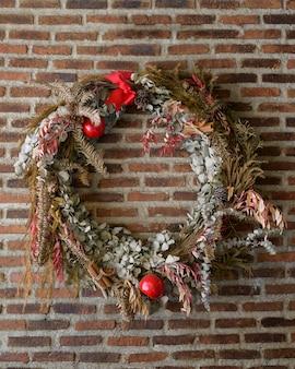 レンガの壁にクリスマスツリーの枝の輪のヒイラギの果実レンガの壁にクリスマスツリーの枝の輪のヒイラギの果実