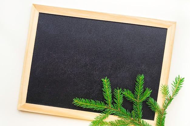 クリスマスツリーの枝は、木製のフレームと黒い黒板の隅にあります。