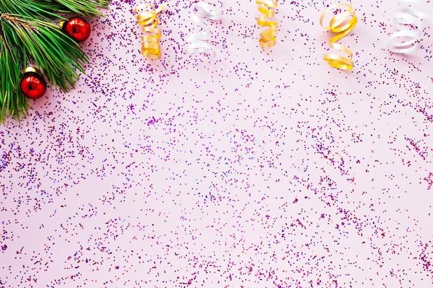 Елочные ветки игрушки и розовые блестки разбросаны