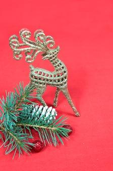 Ветка елки с шишкой и блестящим оленем на красном фоне