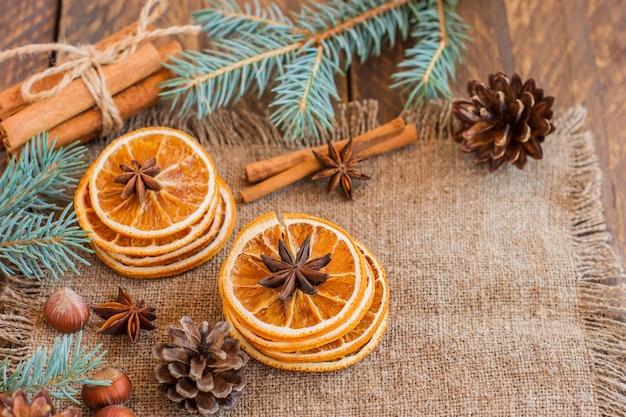 나무 테이블에 말린 오렌지, 계피, 견과류, 아니스 스타가 있는 크리스마스 트리 분기.