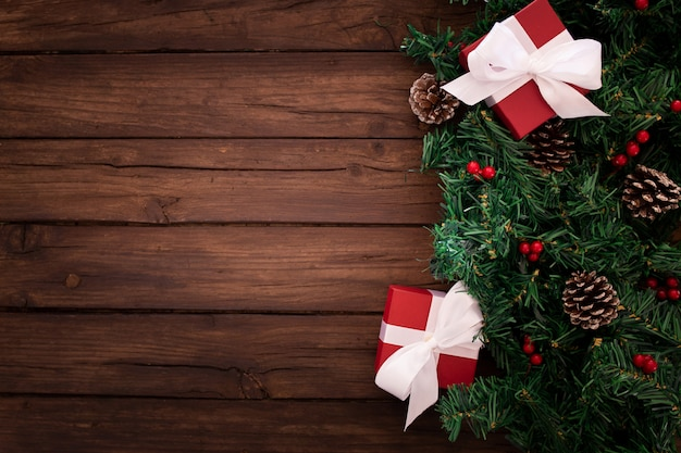 Christmas tree branch with gifts on a wooden background