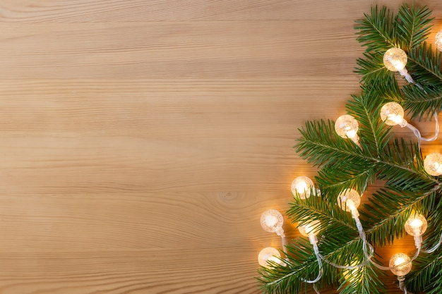 Christmas tree branch with lights on wooden table top, copy space