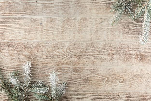素朴な木製のテーブルに松ぼっくりとクリスマスツリーの枝。コピースペースと冬の背景。上面図。フラットレイ