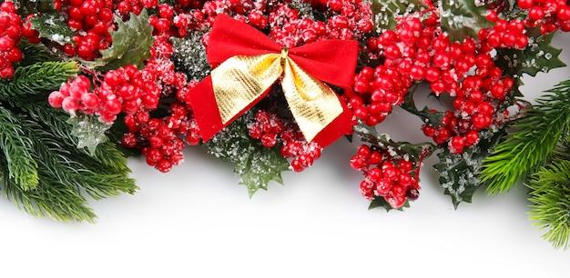 Ветка елки с красными ягодами и бантами