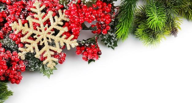 Ветка елки с красными ягодами и золотой снежинкой