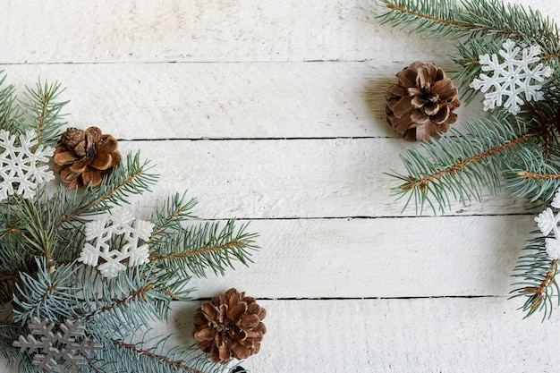 Christmas tree branch with snowflakes and pine cones on white wooden background with copy space