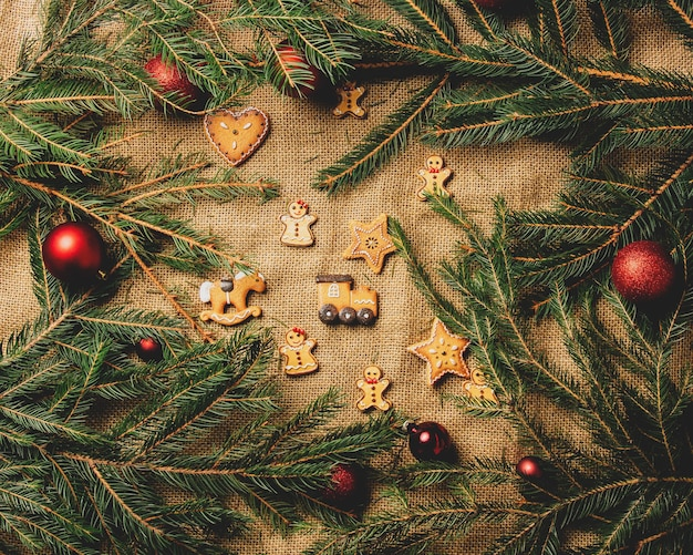 Christmas tree branches and baubles as decration next to cookies on jute background