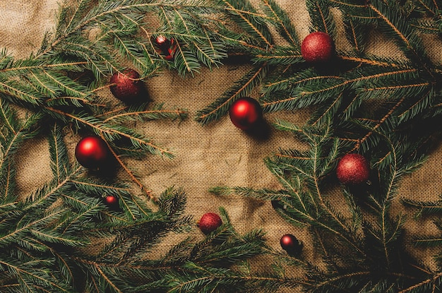 Christmas tree branches and baubles as decration on jute background