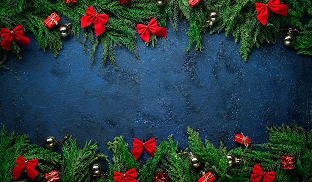 Christmas tree branches and decoration on top and bottom. banner dark blue background copy space.