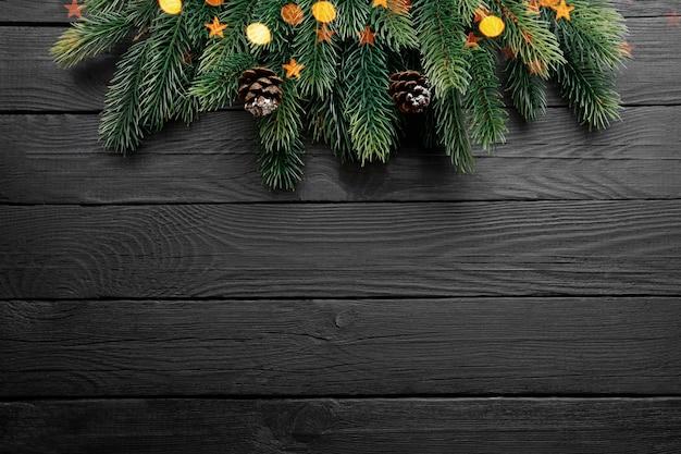 クリスマスツリーの枝、モミの実、黒い木製のテーブルの上の金のライト。上面図、コピースペース