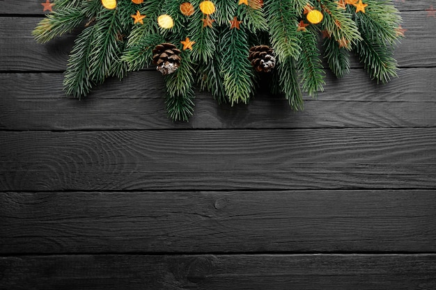 Christmas tree branches, fir cones and gold lights on black wooden table. top view, copy space