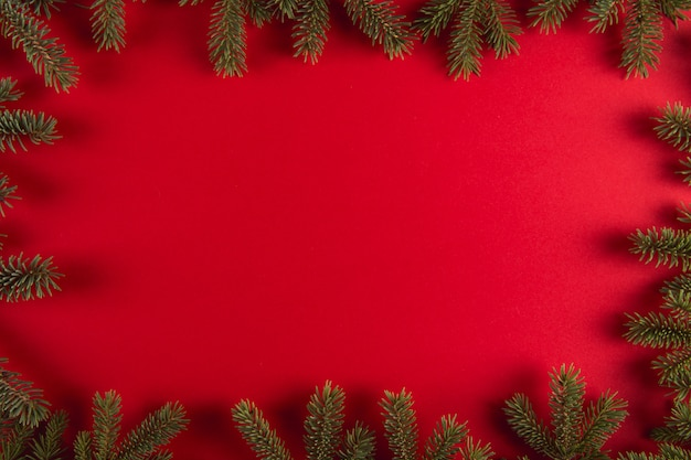 Christmas tree branches in the form of a frame on a red , christmas , greeting card copyspace.
