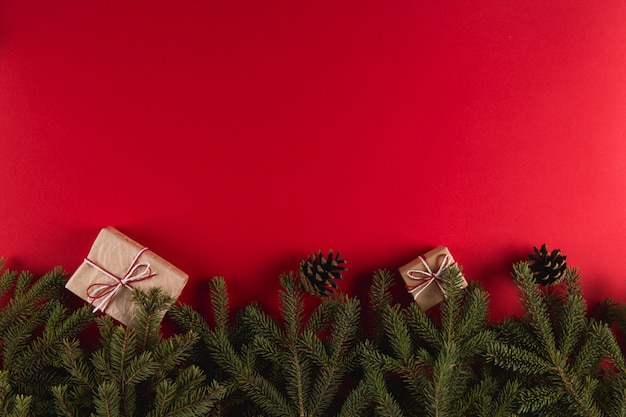 Christmas tree branches, gifts and pine cones on a red , christmas , greeting card copyspace.