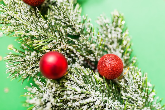 Christmas tree branches on green background with confetti