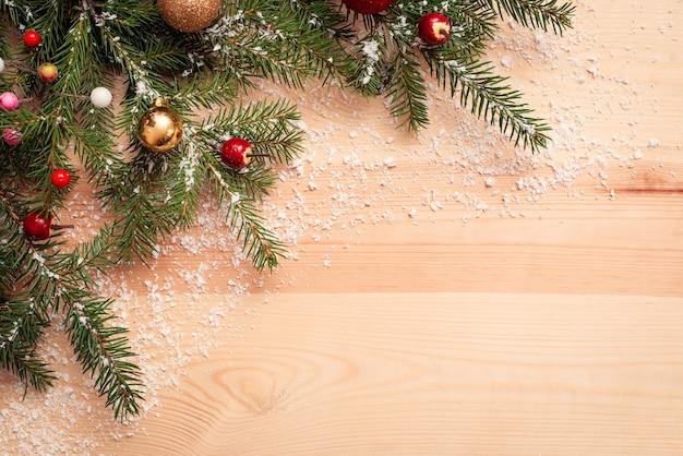 小雪で味付けされた黄色の木製テーブルの上のクリスマスツリーの枝