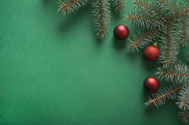 Christmas tree branches, red glass balls on green with copyspace. top view. holiday card.