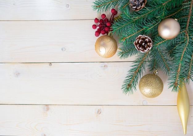 Елочные ветви с яркими рождественскими украшениями на светлом деревянном фоне.