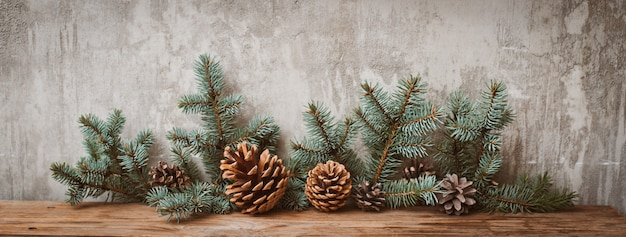 Christmas tree branches with cones on a wooden board against a gray concrete wall.