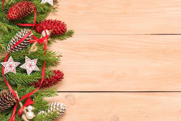 На деревянном столе красиво выложены елочные ветки с украшениями.
