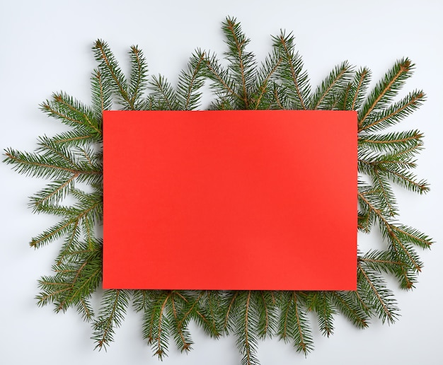 Christmas tree branches with an empty red sheet