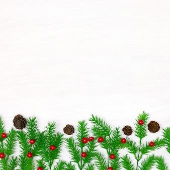 홀리 일렉스 열매와 작은 원뿔이 있는 크리스마스 나무 가지 복사 공간