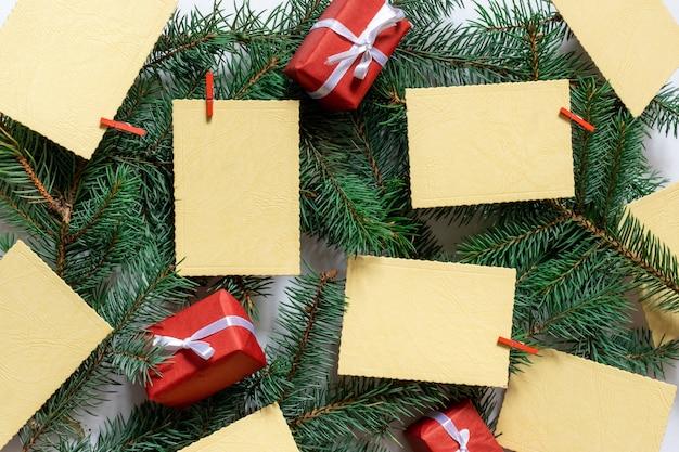 常緑の背景に願いのシートや通知やギフトとクリスマスツリーの枝
