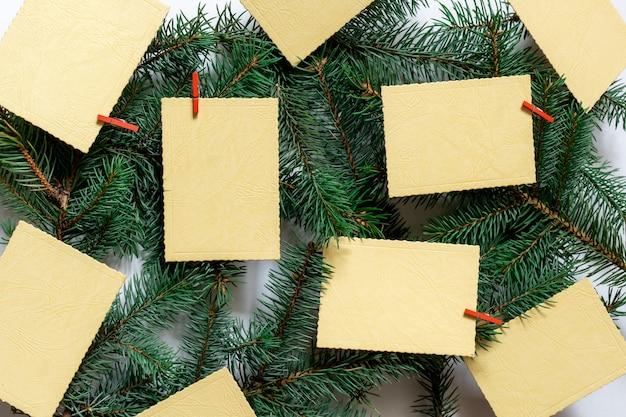 常緑の背景に願いのシートや通知が付いたクリスマスツリーの枝