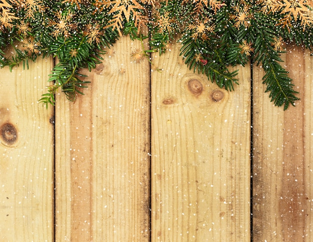 Christmas tree branches on a wooden background with snow overlay