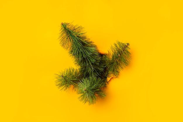 クリスマスツリーは黄色の背景を突破します。新年とクリスマスイブのコンセプト。