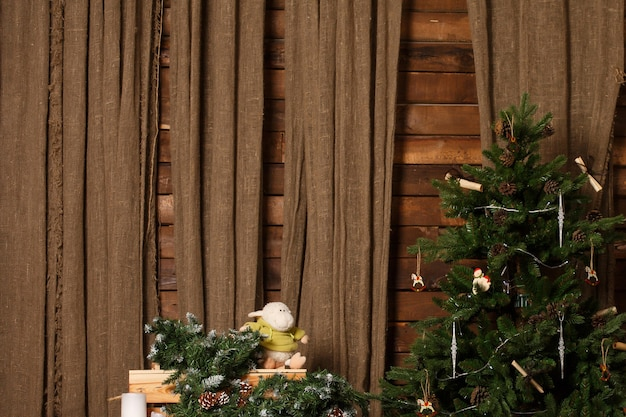 Christmas tree on brown burlap and wooden wall