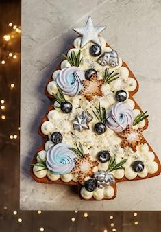 Елочный торт. праздничный сладкий подарок, декор с новогодними огнями.